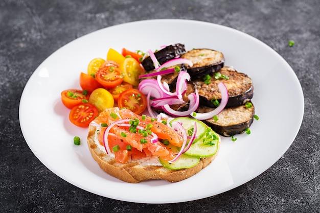 Вкусный бранч бутерброды с лососем, хлебом и сливочным сыром и рукколой, салат из помидоров на темном фоне.