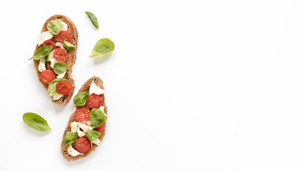 Delicious bruschetta with basil leaves isolated on white surface