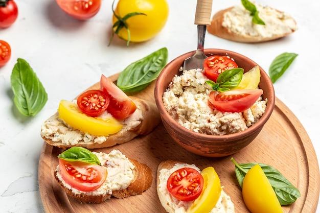 Вкусная брускетта с помидорами, сливочным сыром и листьями базилика на деревянной доске, фоне рецепта еды. закрыть вверх