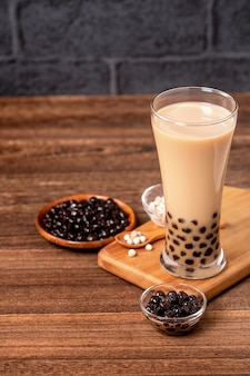Delicious bubble milk tea with tapioca pearl ball in glass on wooden table