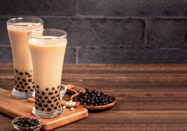 Вкусный пузырьковый чай с молоком с жемчужным шаром тапиоки в стекле на деревянном столе