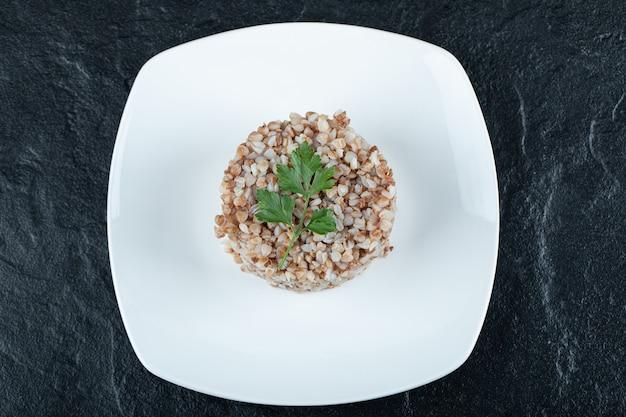 Delizioso grano saraceno con verdure su un piatto bianco
