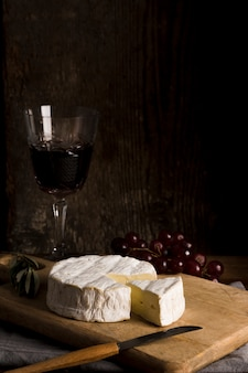 Delicious buffet with cheese and wine on wooden board