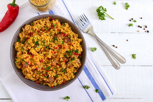 Delicious bulgur with vegetables, meat and greens on a white wooden table. dietary menu. proper nutrition. top view.