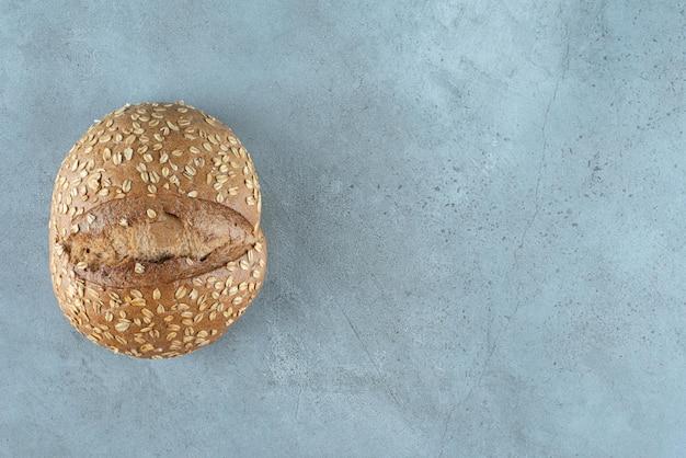 Вкусная булочка с семенами на мраморе.