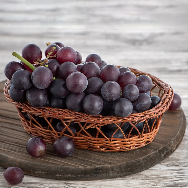 나무 테이블 배경 위에 접시에 포도 과일의 맛있는 무리.