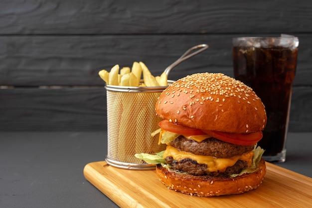 黒い背景、正面図を背景に木の板においしいハンバーガーとフライドポテト