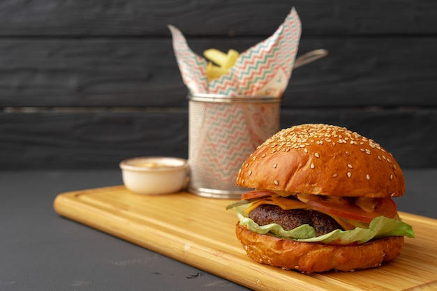 Delicious burger and fries on wooden board against black background