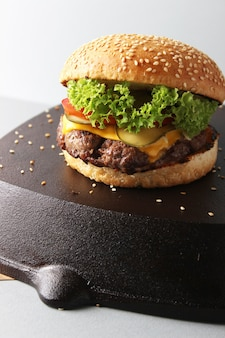 白い表面に隔離された黒い表面のおいしいハンバーガー