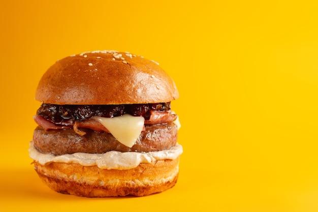 노란색 배경에 맛있는 버거. 치즈와 두 개의 패티를 곁들인 맛있고 신선한 건강에 해로운 버거. 패스트 푸드, 건강에 해로운 음식 개념.