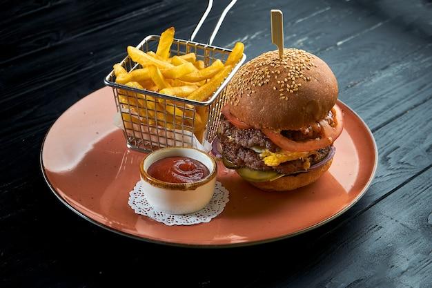 쇠고기, 토마토, 양파 및 노란색 소스를 곁들인 맛있는 햄버거가 콜 슬로우 샐러드와 함께 빨간 접시에 제공됩니다. 미국식 패스트 푸드