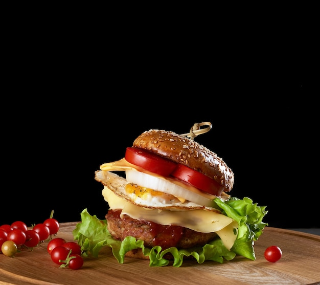 Delicious burger with meat cutlet, cheese, fried egg, tomatoes, cucumber slices and green lettuce, fast food on a round wooden board, black background