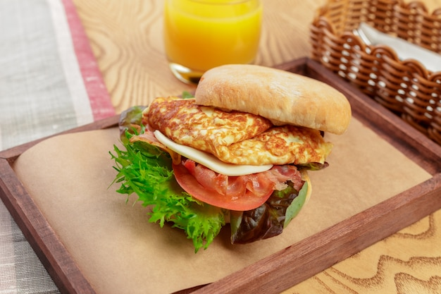 Delicious burger with omelette breakfast dish close up
