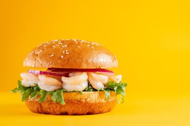 노란색 배경에 분리된 새우가 든 맛있는 버거. 맛있고 신선한 건강에 해로운 햄버거. 가로 배너