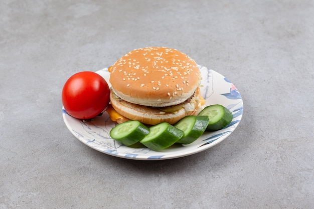 Delicious burger with vegetables on colorful plate