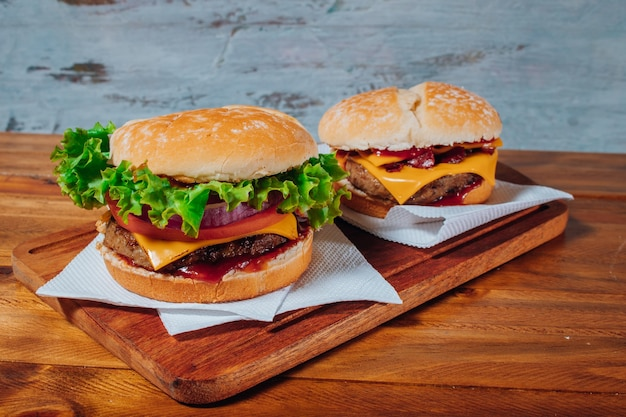 ベーコンとチェダーチーズ、レタス、トマト、赤玉ねぎ、ベーコンとチェダーチーズを自家製パンに、木の表面と素朴な背景に種とケチャップを添えたおいしいハンバーガー。