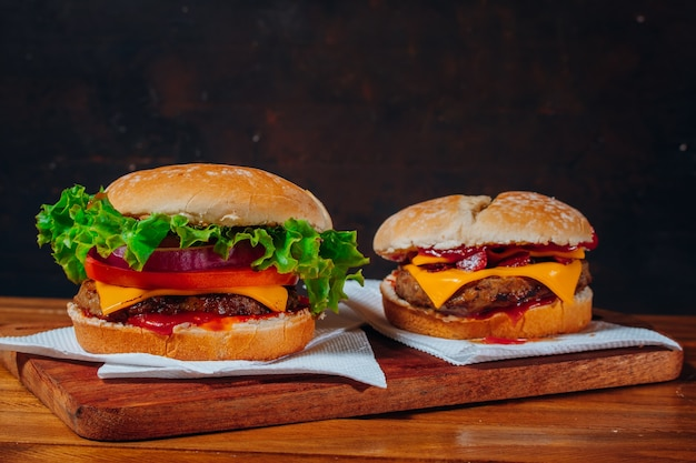 Delicious burgers with bacon and cheddar cheese and with lettuce, tomato and red onion and bacon and cheddar on homemade bread with seeds and ketchup on a wooden surface and black background.