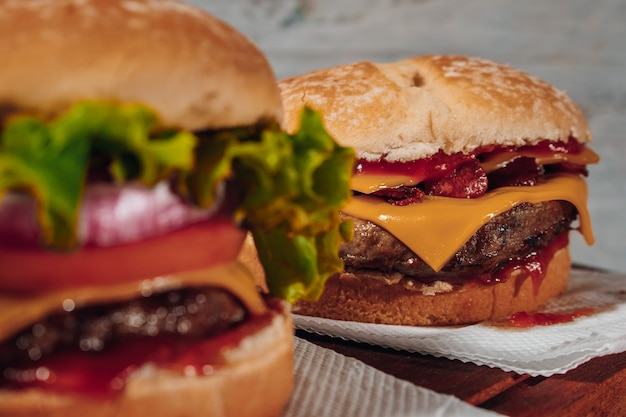 Delicious burgers with bacon and cheddar cheese and with lettuce, tomato and red onion and bacon on homemade bread  and ketchup on a wooden surface and rustic background.. focus in second burguer.