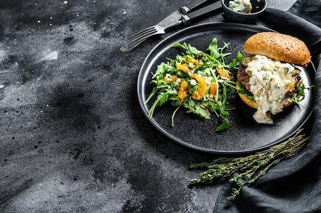 블루 치즈, 베이컨, 차돌박이 쇠고기와 양파 마멀레이드가 들어간 맛있는 버거, 아루 굴라와 오렌지가 들어간 샐러드 반찬. 검정색 배경
