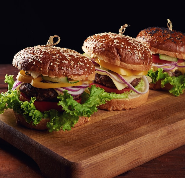 Delicious burgers with fried beef cutlet, tomato, lettuce and onions, crispy white wheat flour bun with sesame seeds. fast food on a wooden board