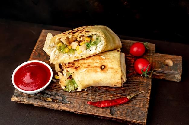 Вкусный буррито в рулетах с курицей, овощами и зеленью на разделочной доске на темном фоне мексиканская шаурма