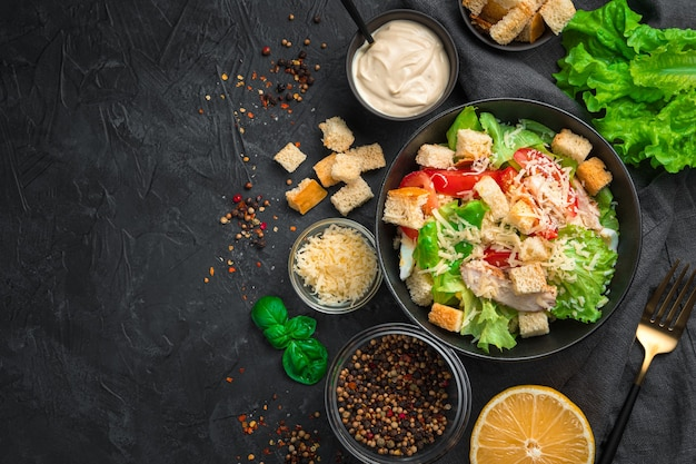 Delicious caesar salad with ingredients, lemon and spices on a black background. top view with copy space.