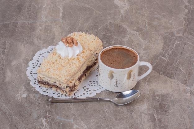 Вкусный торт и чашка кофе на мраморной поверхности.