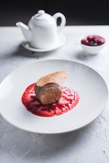 Delicious cake on berries sauce over the ceramic white plate