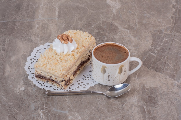 Delicious cake and cup of coffee on marble surface.