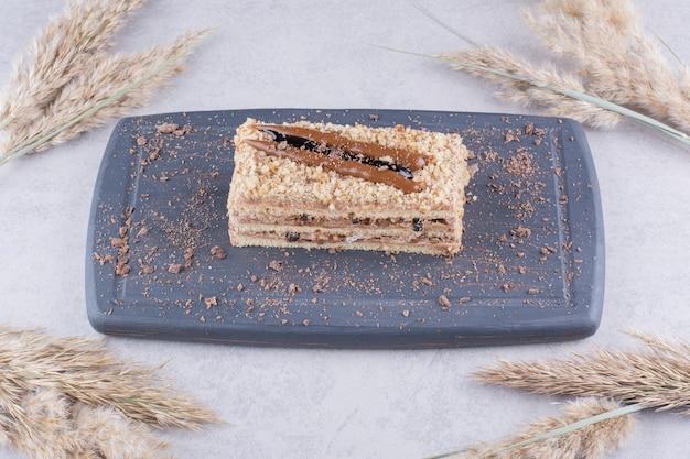 Deliziosa torta sul piatto scuro con spighe di grano.