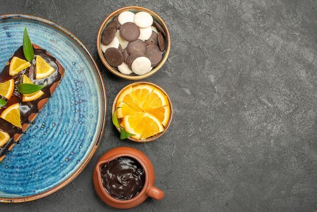 暗いテーブルの映像に他のクッキーとオレンジとチョコレートで飾られたおいしいケーキ