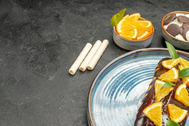 Вкусный торт, украшенный апельсином и шоколадом с другим печеньем на темном столе