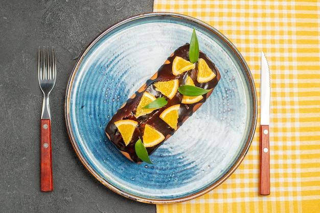 Delicious cake decorated with orange and chocolate served with fork and knife on dark table