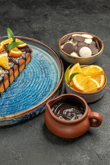 Delicious cake decorated with orange and chocolate with other cookies on dark table footage