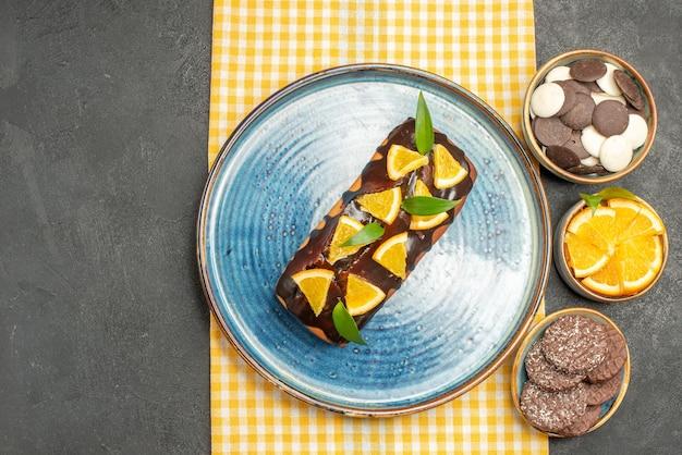 Deliziosa torta decorata con arancia e cioccolato su tovagliolo a strisce gialle e biscotti