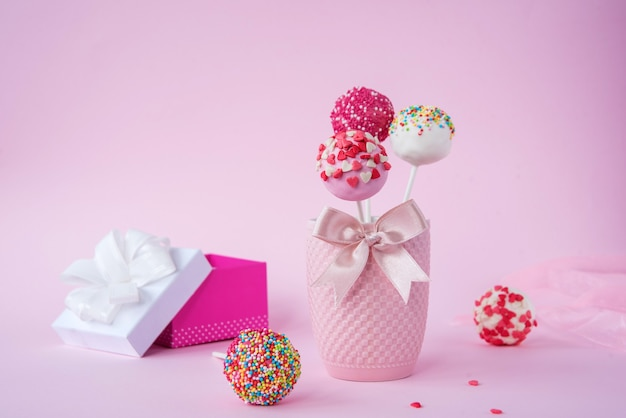 Delicious cake and a gift on a pink background, next to a red and pink ribbon.