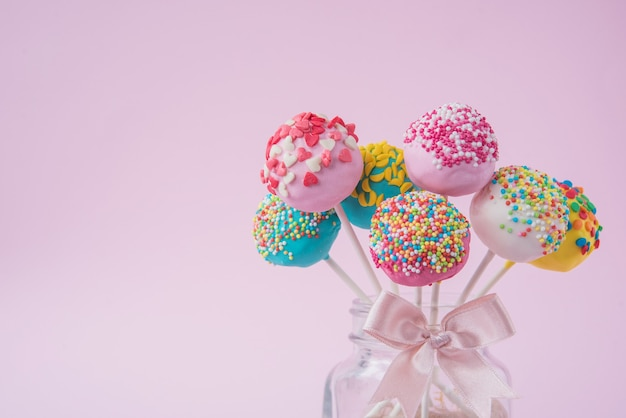 Delicious cake in a glass jar with a bow on a pink background. place to copy text. Premium Photo