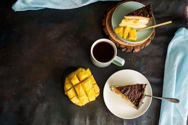 カットのおいしいケーキ、マンゴー、パッションフルーツ、バニラクリーム、ビスケット、卵、フラットレイの層のケーキ。