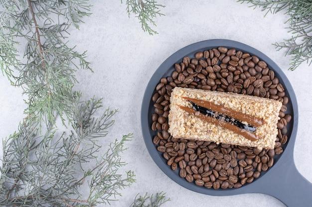 Вкусный торт на темной доске с кофейными зернами. фото высокого качества