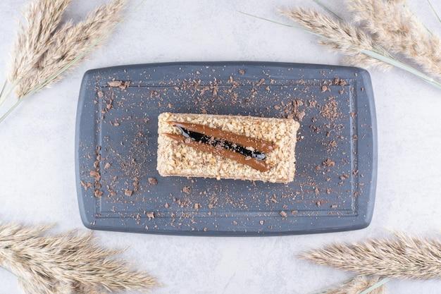 小麦の穂が付いている暗い皿の上のおいしいケーキ。高品質の写真