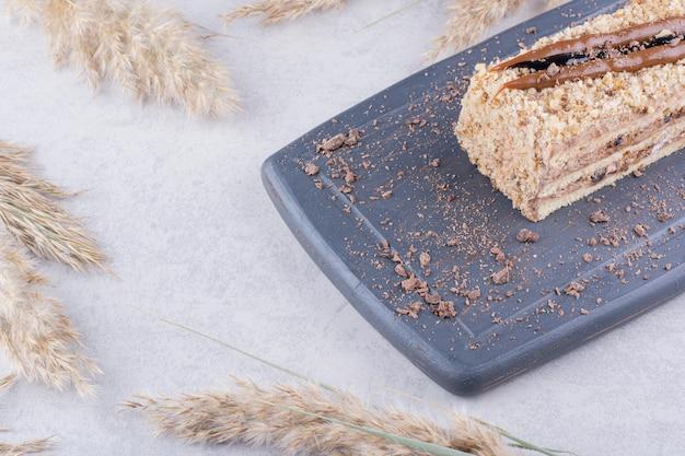 小麦の穂が付いている暗い皿の上のおいしいケーキ。