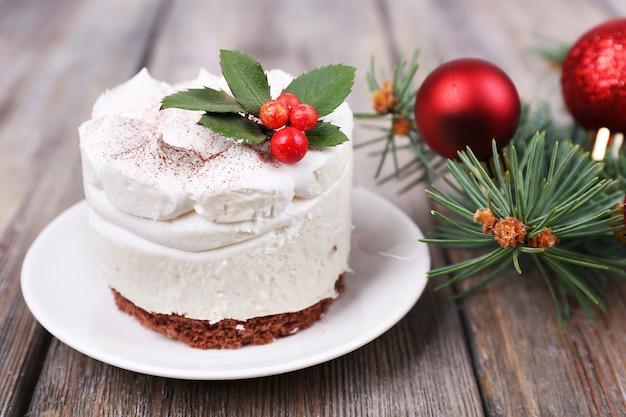 Вкусный торт на блюдце с падубом и ягодами на рождественском украшении и деревянном фоне