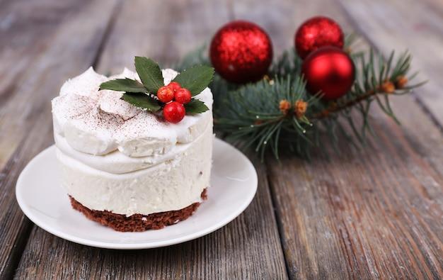 Вкусный торт на блюдце с падубом и ягодами на новогоднее украшение и деревянный стол