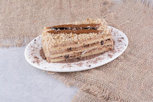 黄麻布と白いプレート上のおいしいケーキ。