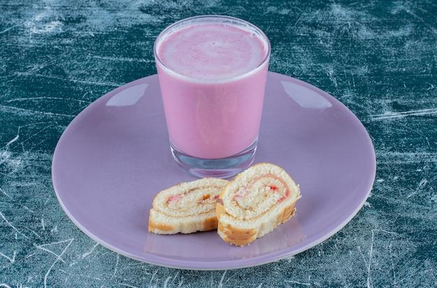 Delizioso frappè di torta e fragole sulla piastra, su sfondo blu. foto di alta qualità