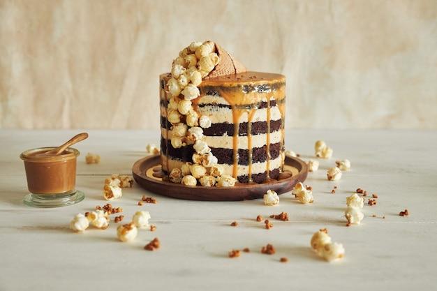 캐러멜 크림을 얹은 맛있는 케이크와 팝콘이 가득한 콘