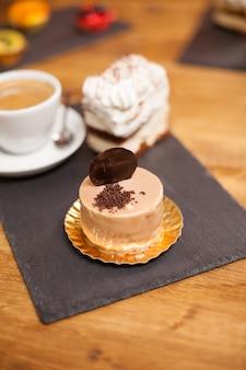 コーヒーショップの木製テーブルの上に茶色の釉薬とおいしいビスケットが乗ったおいしいケーキ。シナモン風味の美味しいケーキ。