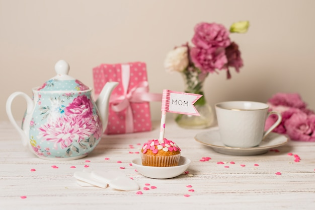 Delicious cake with decorative flag with mom title near teapot, flowers and cup
