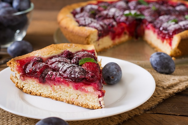 Delicious cake with fresh plums and raspberries
