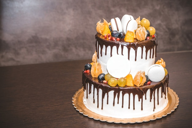 Delicious cake with fruit and berries decoration on wooden table